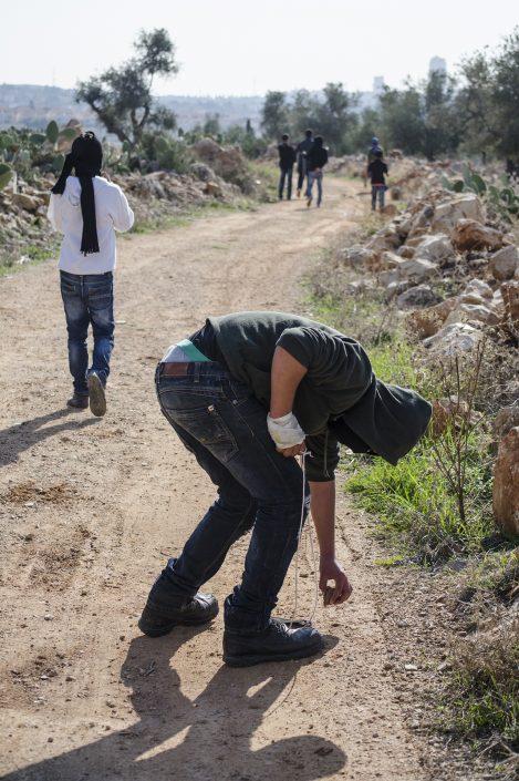 ragazzo palestinese raccoglie una pietra durante la manifestazione