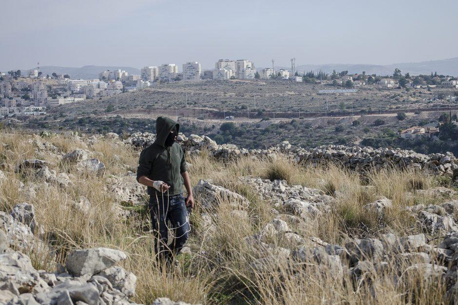 ragazzo palestinese risponde all'assedio isrlaeliano con lancio di pietre